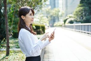 屋外で携帯電話を使うビジネスウーマンの写真素材 [FYI00467027]