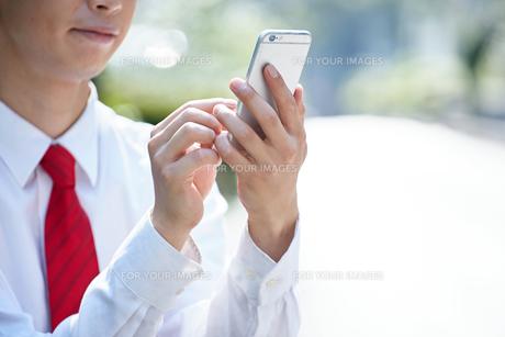 屋外で携帯電話を使うビジネスマンの写真素材 [FYI00467071]