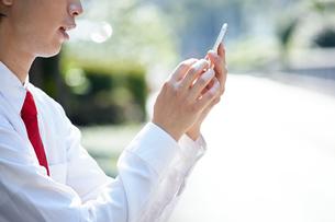 屋外で携帯電話を使うビジネスマンの写真素材 [FYI00467073]