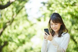 屋外で携帯電話を使う女性の写真素材 [FYI00467076]