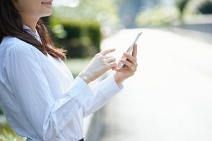 屋外で携帯電話を使うビジネスウーマンの写真素材 [FYI00467079]