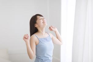 窓際で腕を上げ伸びをする女性の素材 [FYI00467171]