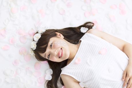 床にまかれた花びらの上に寝転ぶ女性の素材 [FYI00467188]