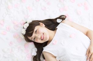 床にまかれた花びらの上に寝転ぶ女性の写真素材 [FYI00467188]