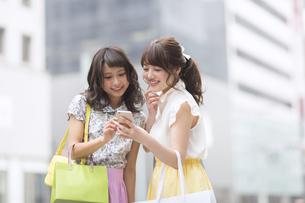 街中でスマートフォンを見る女性2人の素材 [FYI00467191]