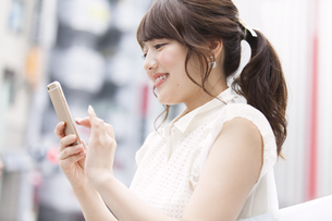 街中でスマートフォンを見る女性の写真素材 [FYI00467193]