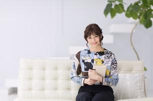 ソファーに座って本を持ち微笑む女性の写真素材 [FYI00467194]