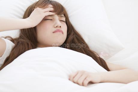 ベッドで頭痛に悩む女性の写真素材 [FYI00467205]