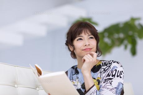 ソファーに座って本を持ち遠くを見つめる女性の写真素材 [FYI00467207]