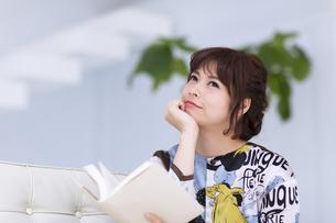 ソファーに座って本を持ち考え込む女性の写真素材 [FYI00467208]