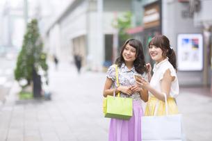 街中でスマートフォンを持ち微笑む女性2人の素材 [FYI00467210]