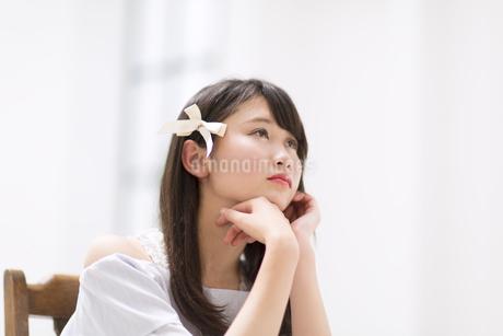 頬に両手を当て考え事をする女性の素材 [FYI00467216]