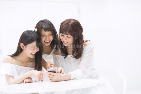 スマートフォンを見て笑う女性3人の写真素材 [FYI00467217]