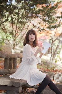秋の紅葉した公園のベンチで読書をする女性の素材 [FYI00467228]