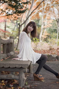 秋の紅葉した公園のベンチで座っている女性の素材 [FYI00467230]