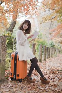 秋の紅葉した公園でトランクに座って本を読む女性の素材 [FYI00467250]