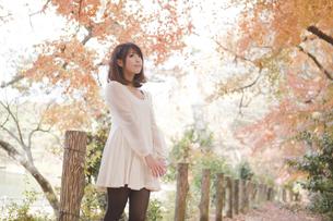 秋の紅葉した公園で立ってペットボトルを持っている女性の素材 [FYI00467253]
