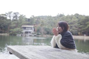 公園のテーブルに肘を付くニットセーターを着た女性の素材 [FYI00467255]