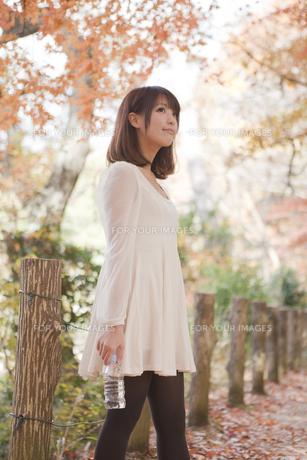 秋の紅葉した公園で立ってペットボトルを持っている女性の素材 [FYI00467257]