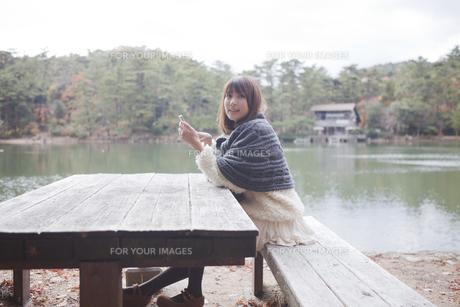 公園のテーブルで携帯をさわるニットセーターを着た女性の素材 [FYI00467262]