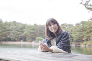 公園のテーブルで携帯をさわるニットセーターを着た女性の素材 [FYI00467266]