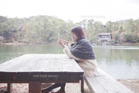 公園のテーブルで携帯をさわるニットセーターを着た女性の素材 [FYI00467267]