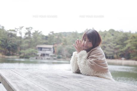 公園のテーブルに肘を付くニットセーターを着た女性の素材 [FYI00467271]