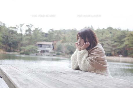 公園のテーブルに肘を付くニットセーターを着た女性の写真素材 [FYI00467277]
