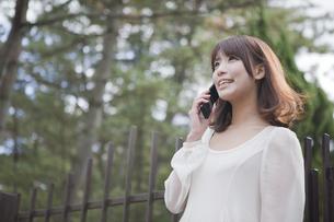 建物の前で電話をする女性の素材 [FYI00467279]