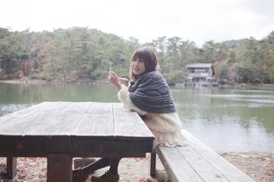 公園のテーブルで携帯をさわるニットセーターを着た女性の素材 [FYI00467280]