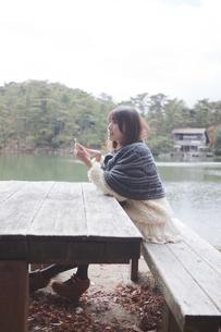 公園のテーブルで携帯をさわるニットセーターを着た女性の素材 [FYI00467281]