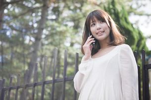 建物の前で笑顔で電話をする女性の素材 [FYI00467283]