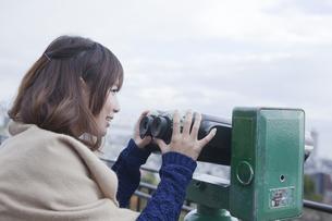 展望台から双眼鏡で神戸の景色を望む笑顔の女性の素材 [FYI00467300]