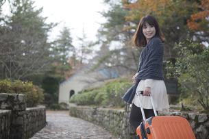 秋の石畳をトランクを引いて歩く笑顔の女性の素材 [FYI00467301]