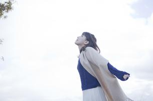 高台で伸びをするストールを巻いた女性の素材 [FYI00467304]
