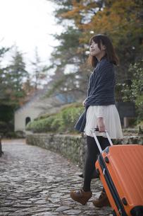 秋の石畳をトランクを引いて歩く笑顔の女性の素材 [FYI00467308]