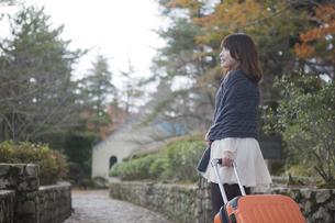 秋の石畳をトランクを引いて歩く笑顔の女性の素材 [FYI00467310]
