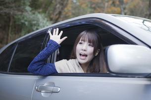 秋の紅葉の公園の駐車場で車の運転をする女性の写真素材 [FYI00467312]
