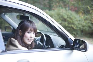 秋の紅葉の公園の駐車場で車の運転をする女性の写真素材 [FYI00467320]