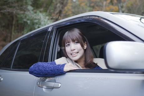 秋の紅葉の公園の駐車場で車の運転をする女性の写真素材 [FYI00467321]