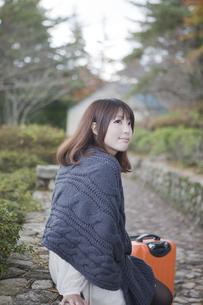 秋の石畳にトランクを置いて座っている笑顔の女性の素材 [FYI00467323]