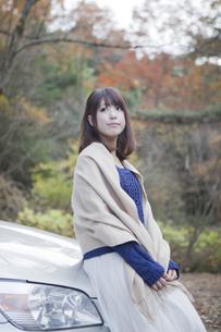 秋の紅葉の公園の駐車場で車の前で立つ女性の写真素材 [FYI00467329]