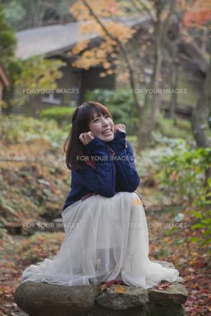 秋の紅葉の公園で座っている笑顔の女性の写真素材 [FYI00467359]