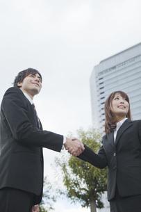 ビルの前で握手をするビジネスウーマンとビジネスマンの写真素材 [FYI00467391]