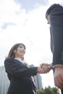 ビルの前で握手をするビジネスウーマンとビジネスマンの写真素材 [FYI00467418]