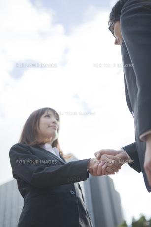 ビルの前で握手をするビジネスウーマンとビジネスマンの写真素材 [FYI00467422]
