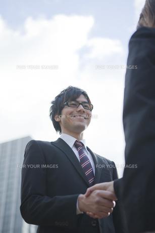 ビルの前で握手をするビジネスウーマンとビジネスマンの写真素材 [FYI00467424]