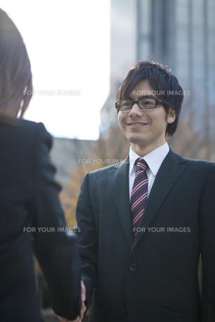 ビルの前で握手をするビジネスウーマンとビジネスマンの写真素材 [FYI00467437]