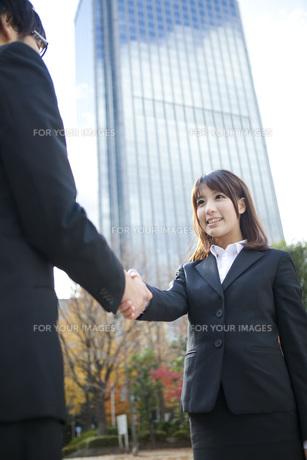 ビルの前で握手をするビジネスウーマンとビジネスマンの写真素材 [FYI00467441]