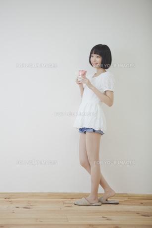 コップを持って立っている女性の素材 [FYI00467509]